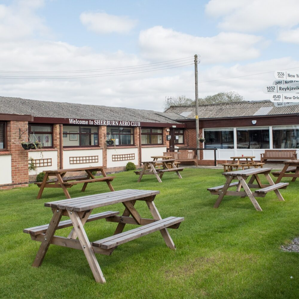 Picnic benches and outdoor space by the restaurant at Sherburn Aero Club
