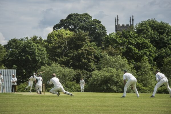 Cricket players, trees a Church in background
