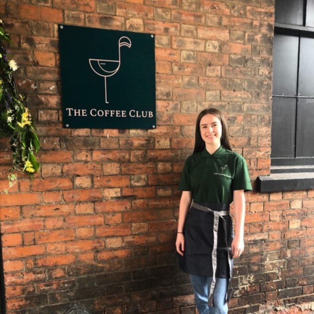 Coffee Club staff member standing outside the entrance