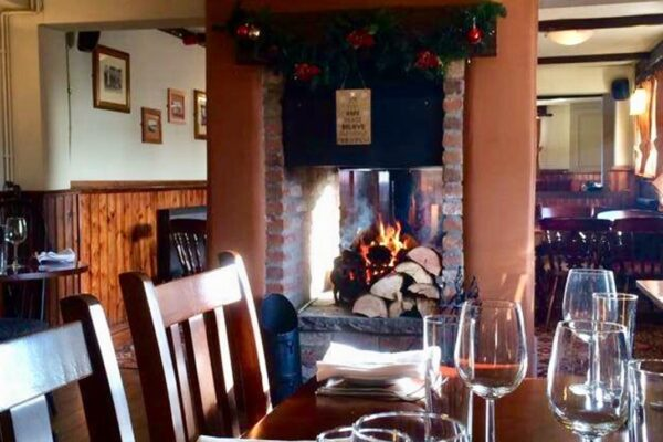 Table set for dinner in front of the fireplace at The Drovers Arms in Skipwith