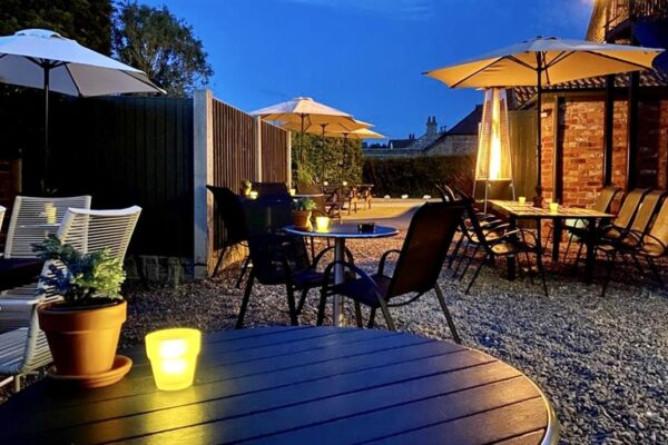 Outdoor area at The Drover's Arms in Skipwith with tables, candles and heaters