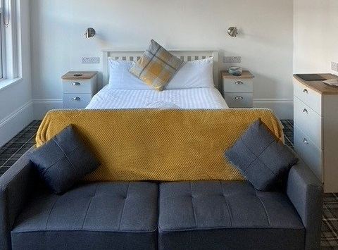 A double bed and couch in Hazeldene bed and breakfast