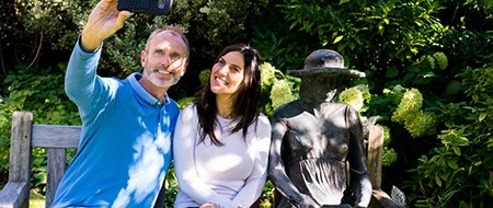 A couple sat next to a sculpture of a lady sat on a bench at Stillingfleet Lodge Gardens