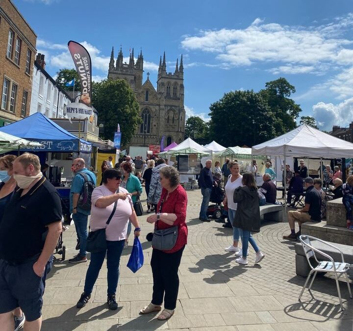 Stalls at Selby Farmers Market, with Selby Abbey in the background